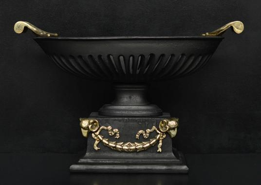 A cast iron bowl grate with brass rams heads