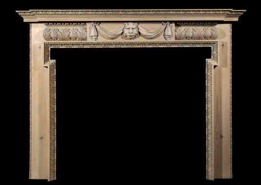 A carved pine fireplace with lion's mask and drapery