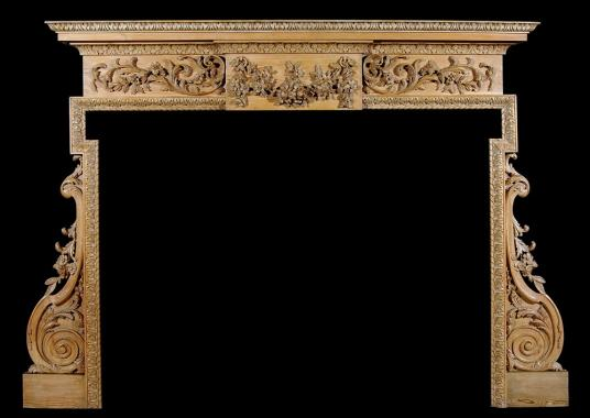 A carved English George III style pine fireplace