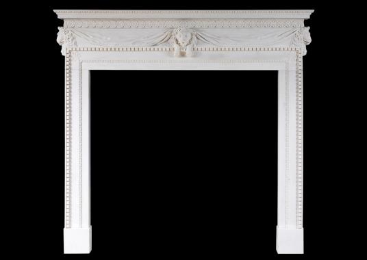 A white marble fireplace with carved lion's mask