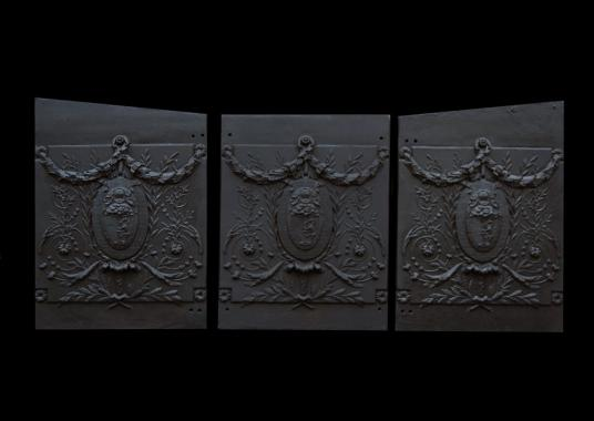A set of three decorative cast iron fireplace interiors