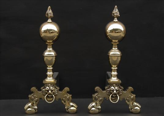 A pair of brass firedogs with flame finials
