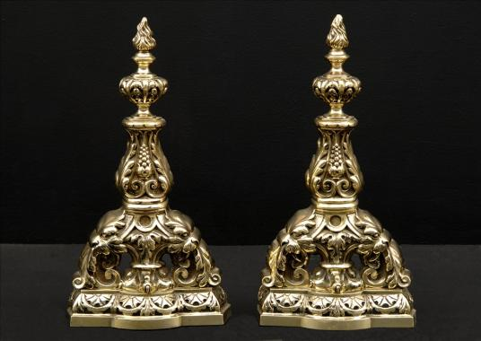 A pair of decorative brass firedogs