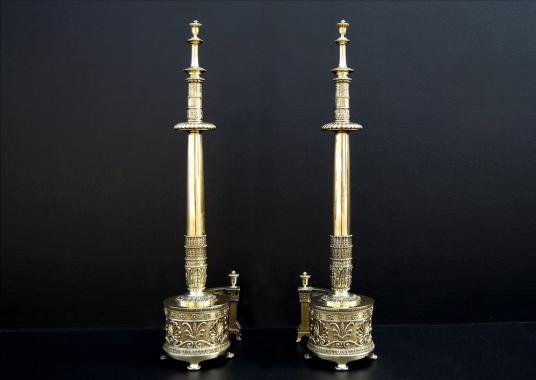 A impressive pair of English Regency brass firedogs with Aethenian leaves