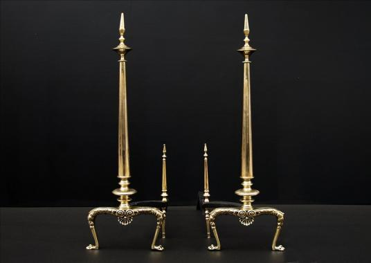 A pair of tapering brass firedogs