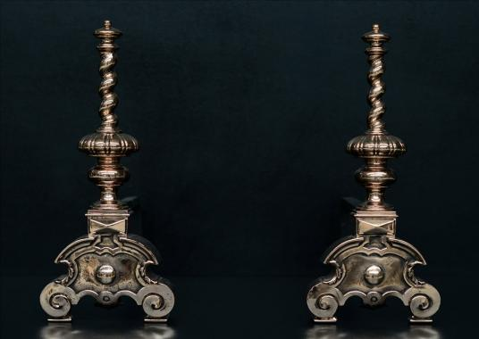 A pair of bronze firedogs with barley twist tops
