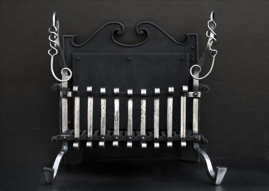 An Arts and Crafts polished wrought iron firegrate