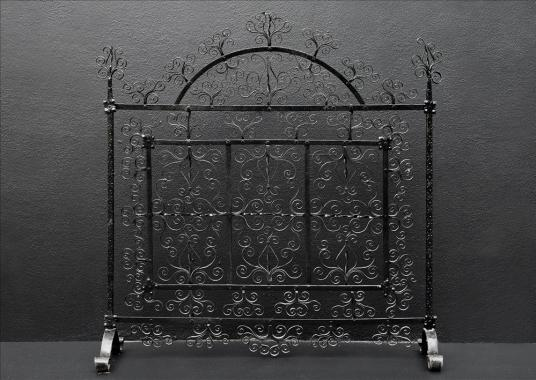 A delicately scrolled wrought iron firescreen