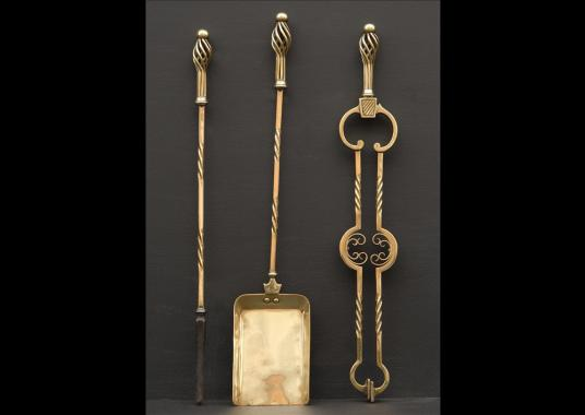 A set of late 19th century Arts and Crafts brass firetools
