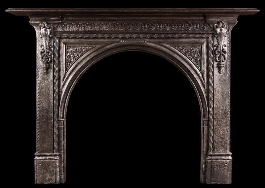 A 19th century iron fireplace with arched opening
