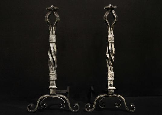 A large pair of polished wrought iron firedogs