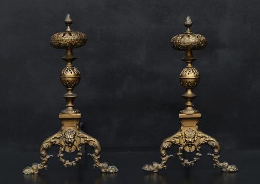 A pair of ornate brass firedogs