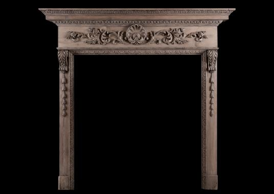 A carved pine fireplace with shell to centre