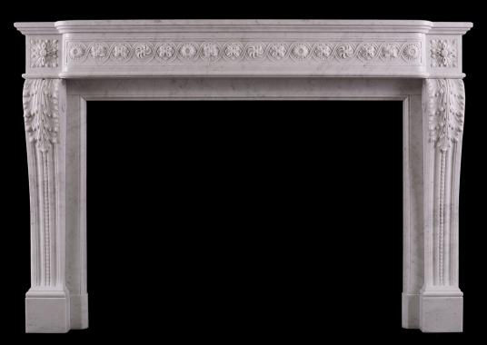 A carved marble fireplace in the Louis XVI manner