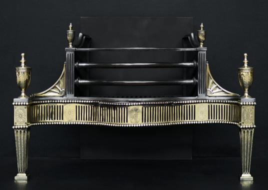 A Georgian style brass and steel firegrate
