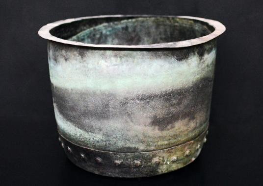 A large copper coal bucket with verdigris patination