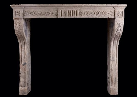 A rustic Louis XVI stone fireplace