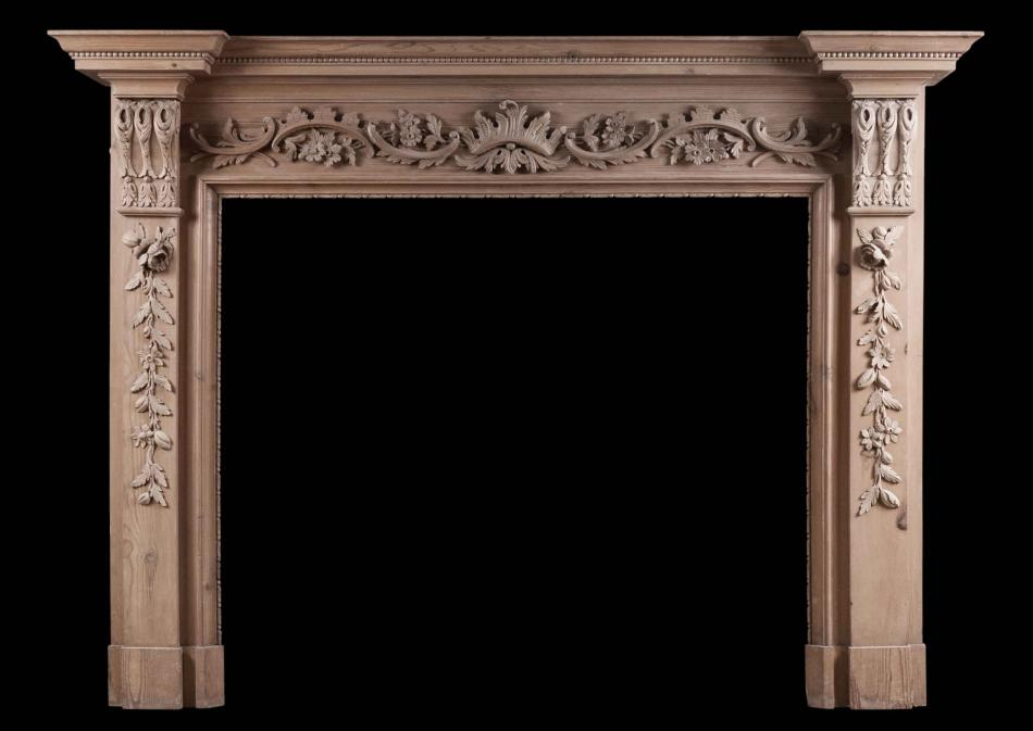 An English pine fireplace with carved fruit and foliage