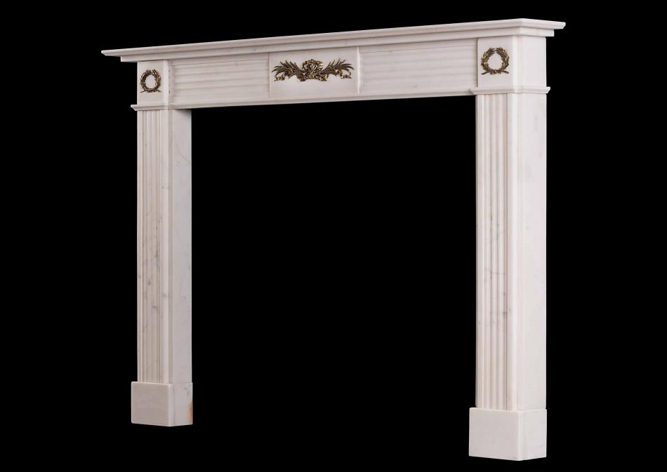 A Regency style Statuary marble fireplace with brass ormolu enrichments