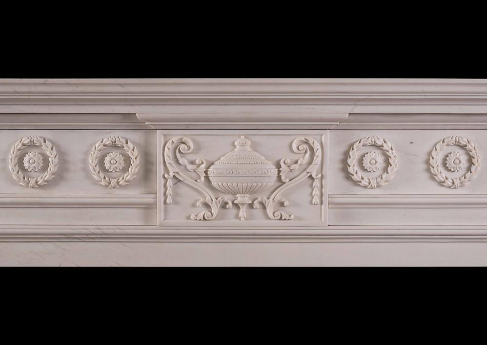 A late Georgian style carved chimneypiece in white marble