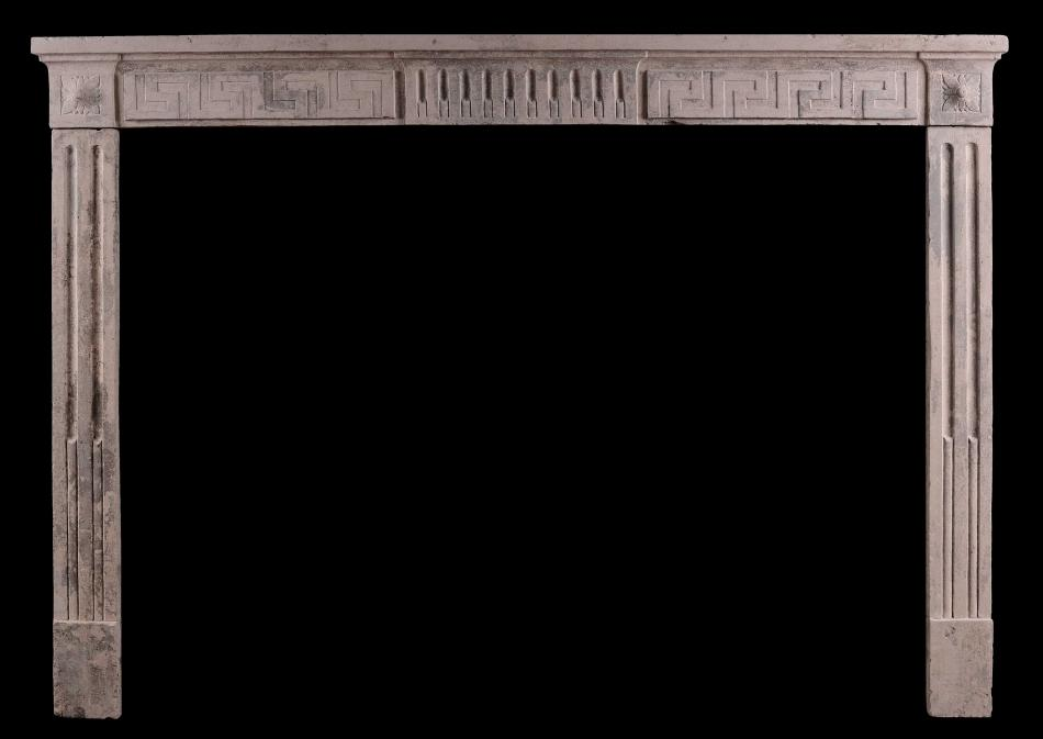 A rustic 18th century Louis XVI fireplace with Greek key motif