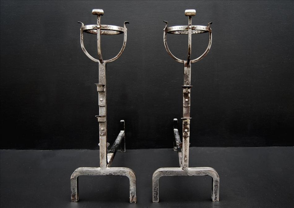 A pair of steel firedogs with mulling tops