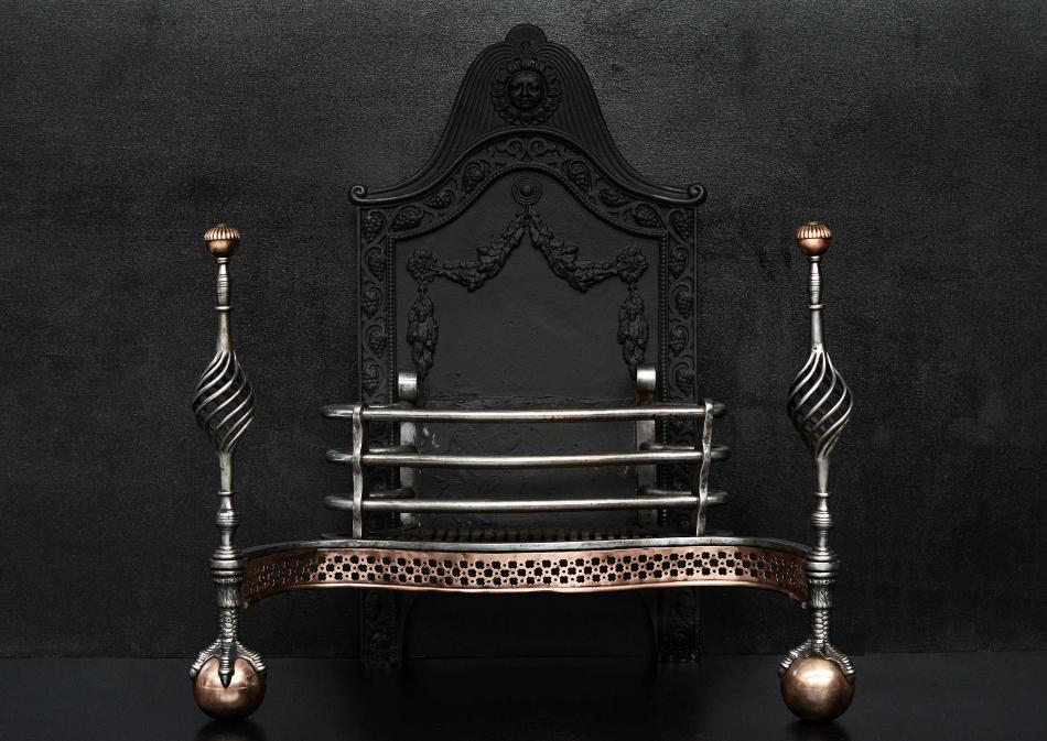 An English cast iron and steel firegrate with decorative back