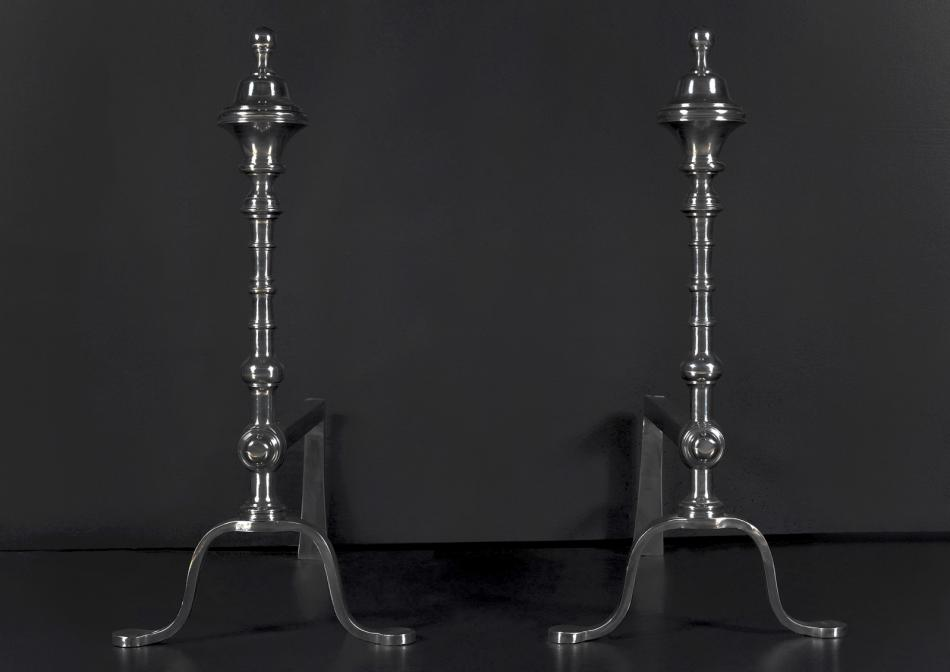 A pair of elegant polished steel firedogs