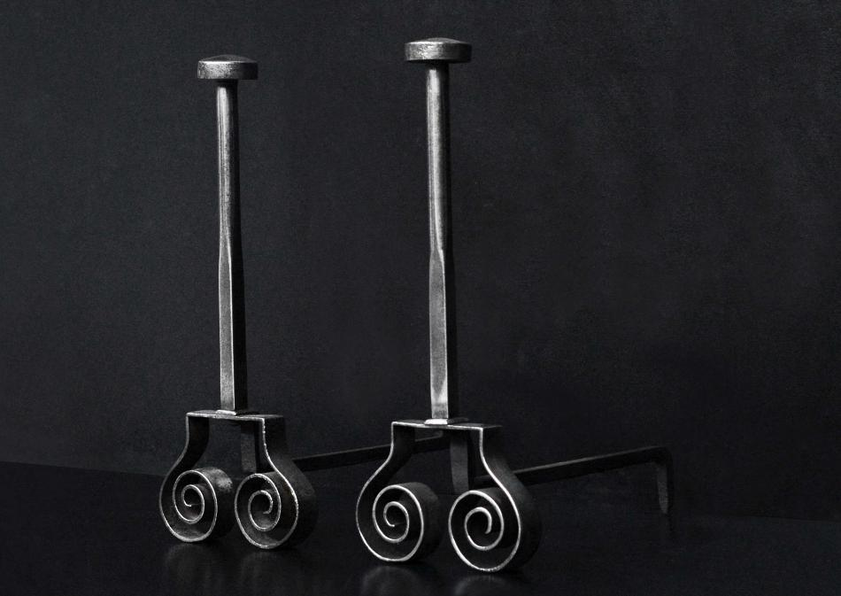 A pair of polished steel firedogs with scrolled feet