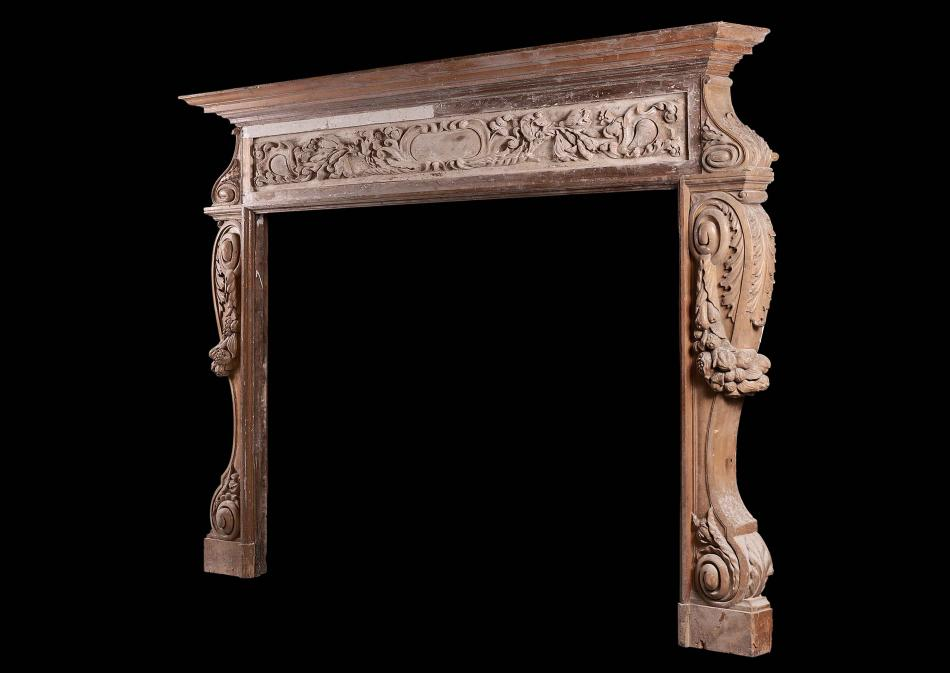A large and rustic antique wood fireplace with carved fruit and foliage