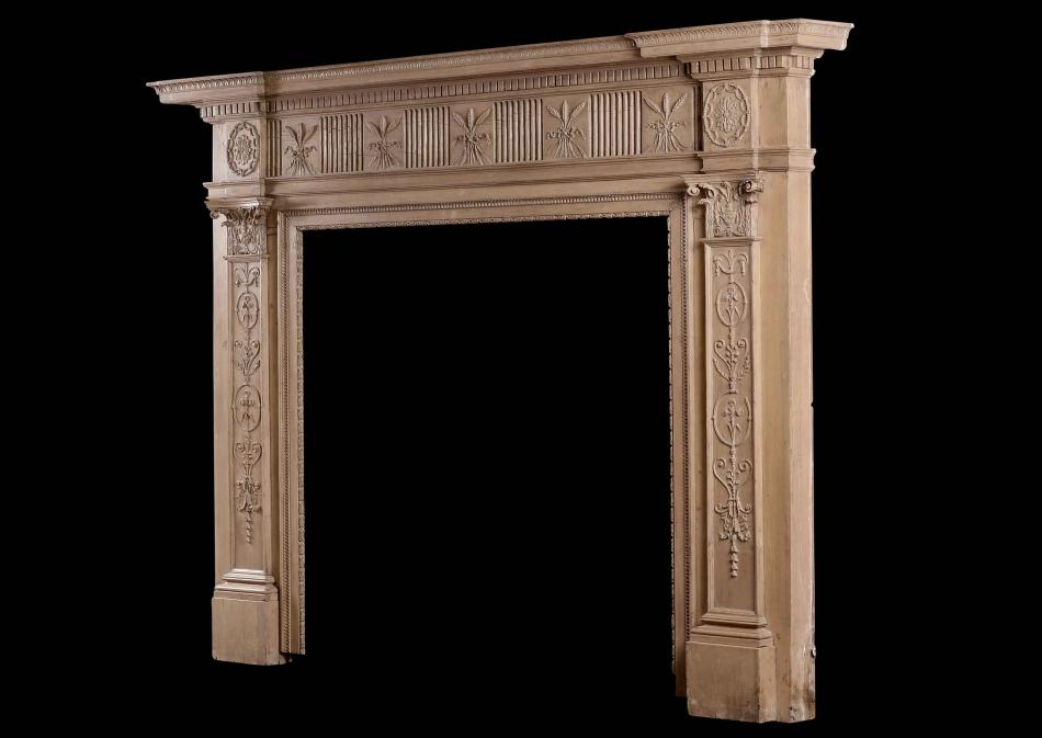 An 18th century carved pine fireplace in the Adam style