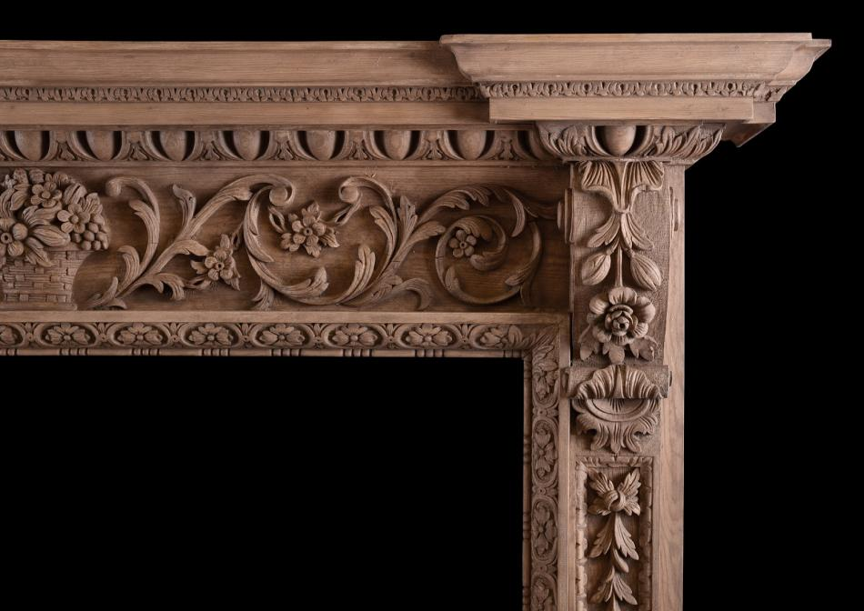An ornate pine fireplace with carving throughout
