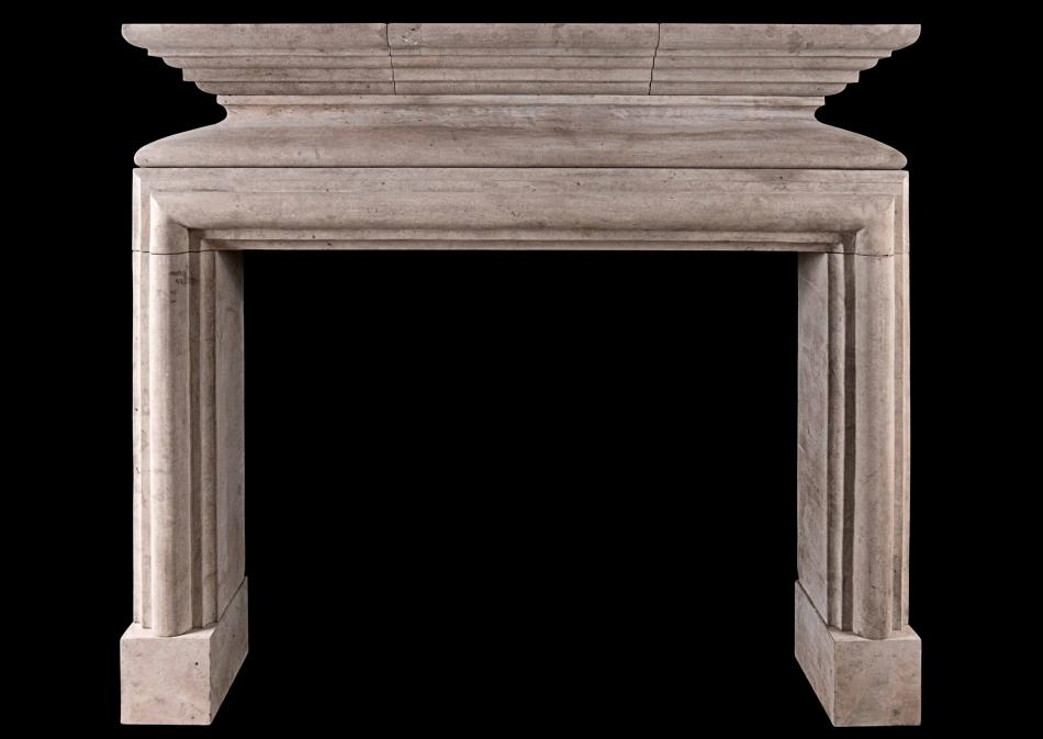 A rustic French Louis XIII style limestone fireplace