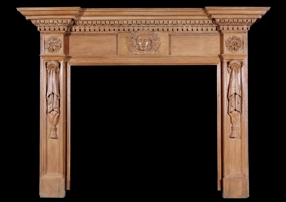 A 19th century English oak fireplace with carved mask to centre