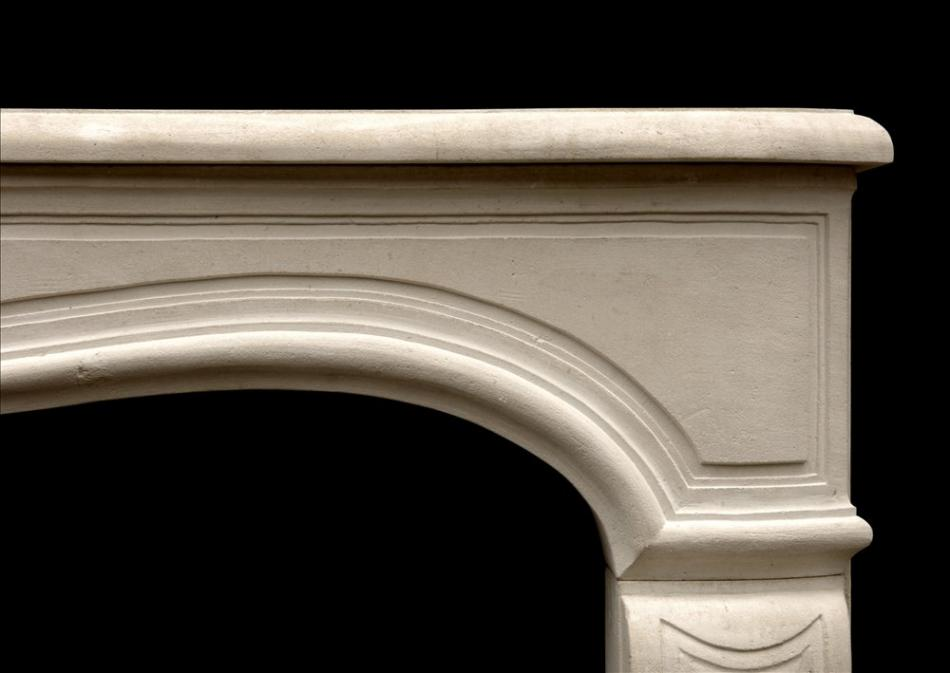 A 20th century Louis XV style limestone fireplace
