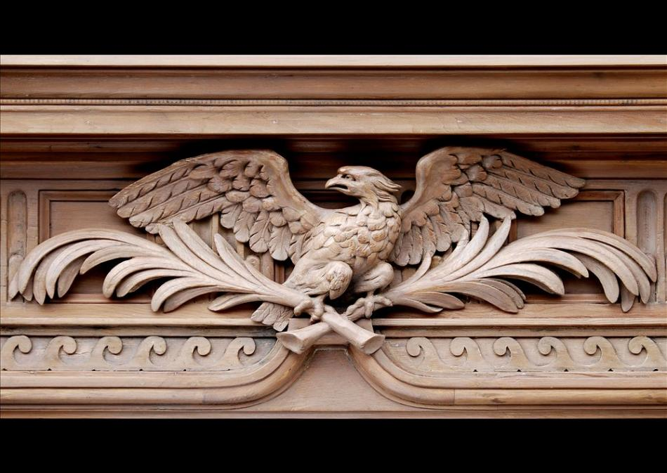A Neo-Classical English pine fireplace with carved eagle to frieze