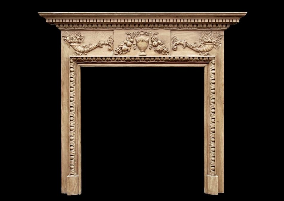 An English Georgian style pine fireplace with gesso enrichments