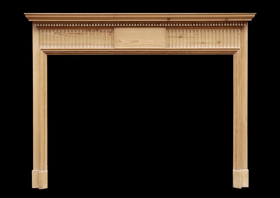 An English pine fireplace with fluted frieze