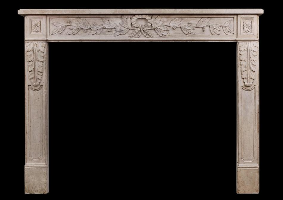 An  ornately carved French limestone fireplace in the Louis XVI style