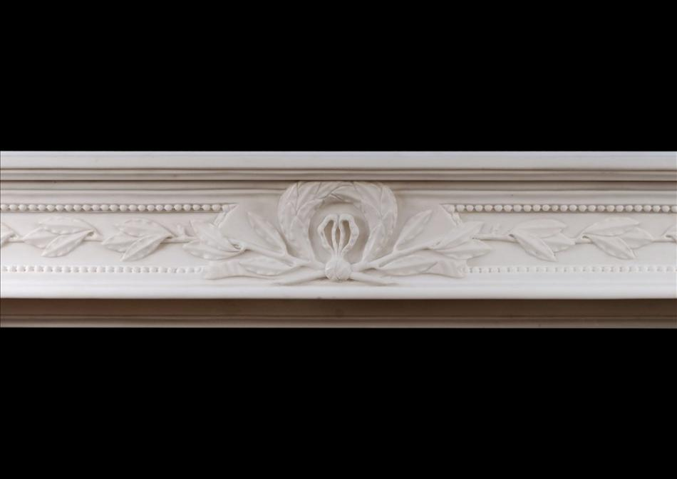 A carved French Louis XVI style white marble fireplace