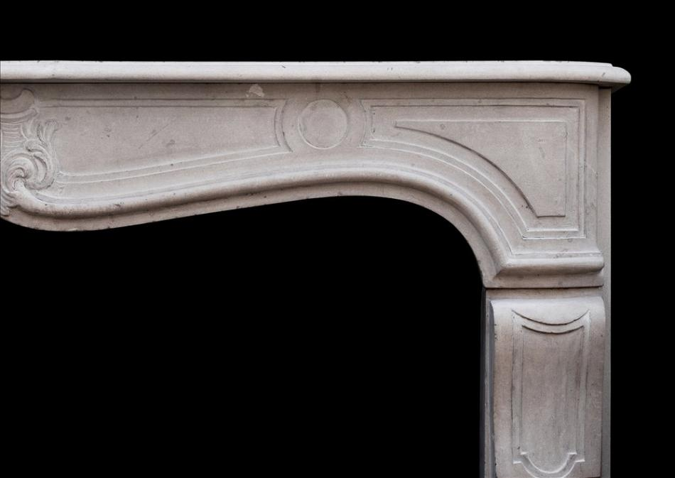 A 19th century French Louis XV style limestone fireplace