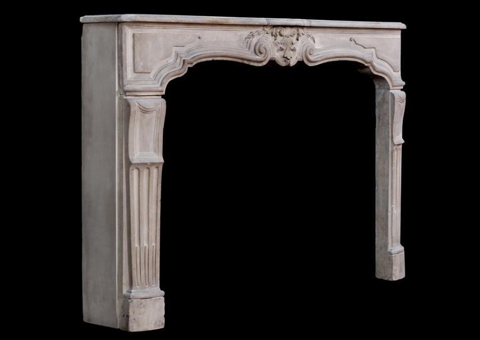 An antique French Louis XV limestone fireplace. 18th century
