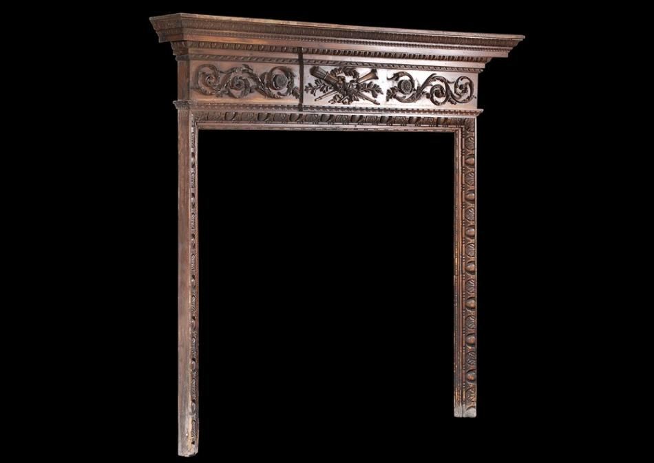 A late 18th century carved pine English fireplace