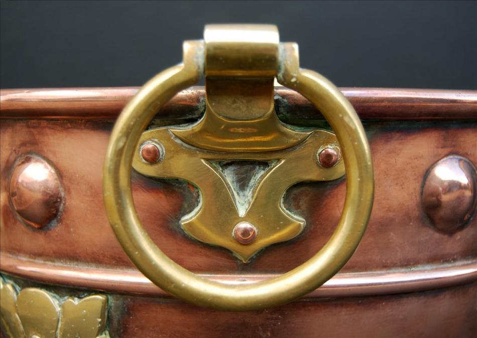 A small copper coal bucket with brass embellishments