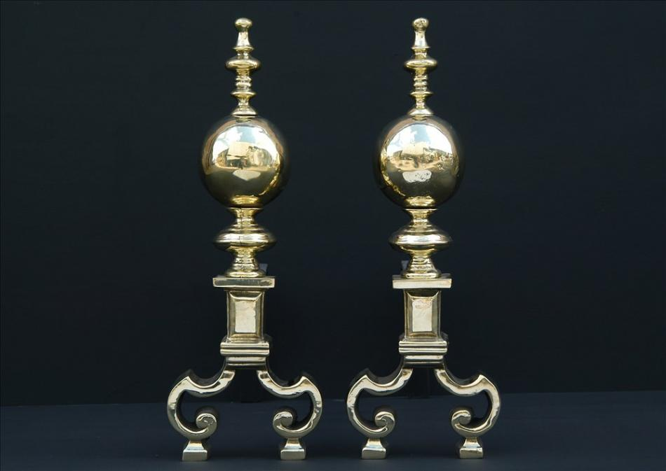 A pair of brass firedogs with ball finials