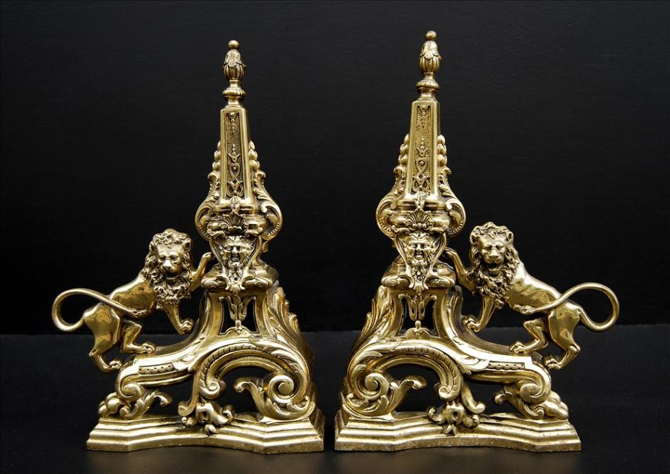 A pair of brass firedogs with lions