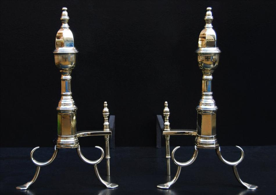 A pair of English brass firedogs with hexagonal shafts