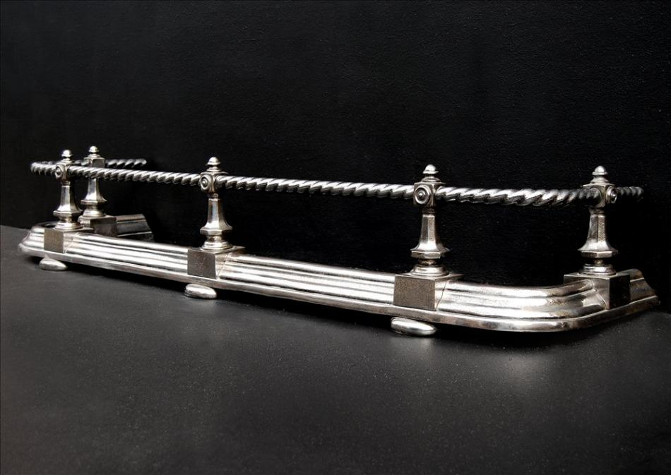 A polished steel fender with rope moulded top bar
