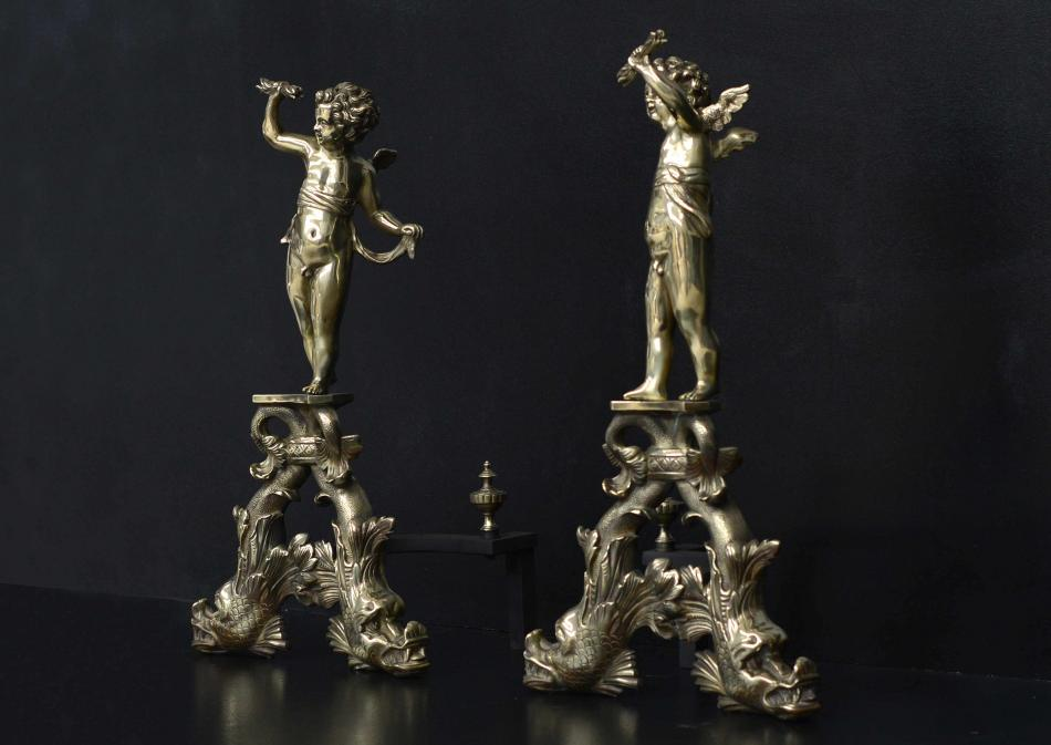 A large pair of brass firedogs with cherubs