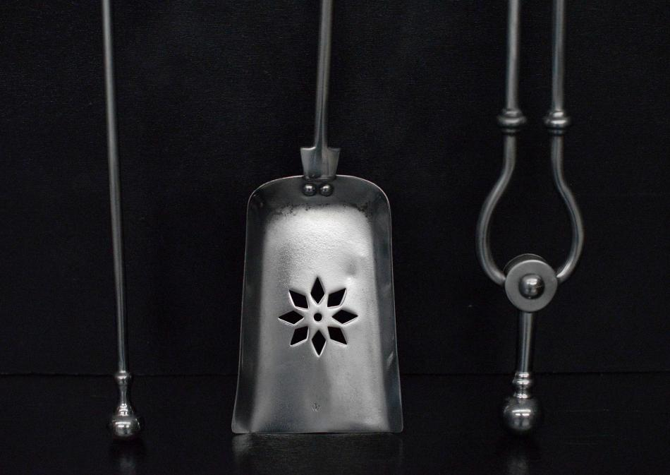 A set of polished steel firetools